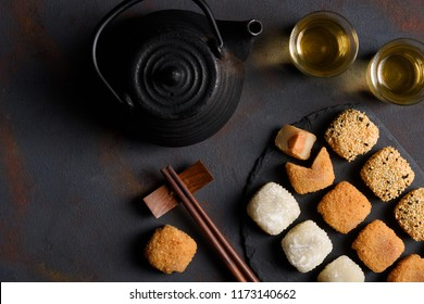 Mochi assortment with wooden chopticks and tea traditional japanese rice dessert flat lay top view