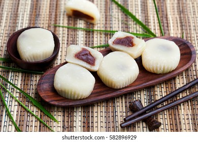 Mochi cake with red beans on wooden plate with bamboo leaves. Traditional Japanese dessert