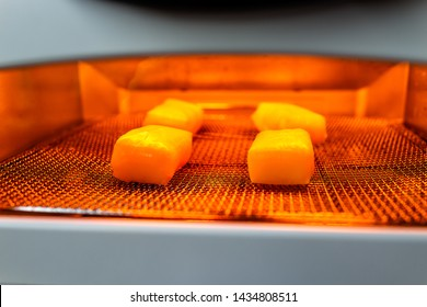 Mochi rice cake squares being baked in toaster oven in traditional Japanese way with light inside on rack