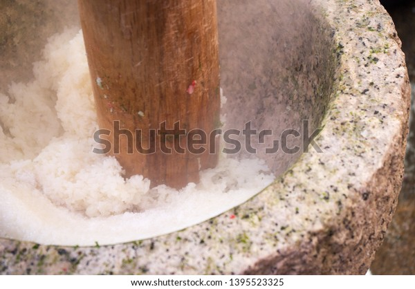 Mochigome glutinous rice being pounded into a thick, malleable, elastic dough for mochi rice cakes during Mochitsuki ceremony at a local household in Shiga prefecture, Japan before the New Year