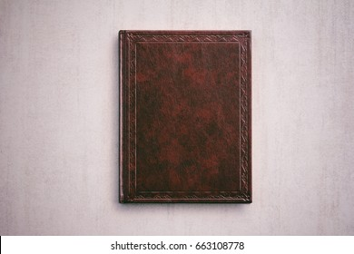 mock up for the Bible, Koran. the book in a red cover on a light gray background, top view