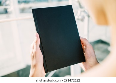 Mock up of black book holding young woman`s  hands
