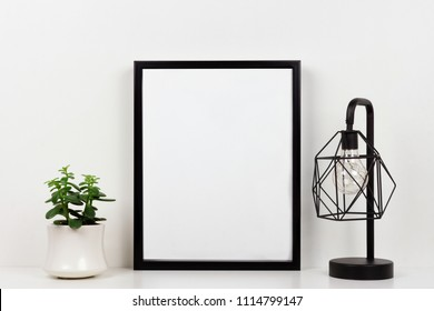 Mock up black frame, succulent plant and industrial style lamp on a shelf or desk. White shelf and wall. Portrait frame orientation.