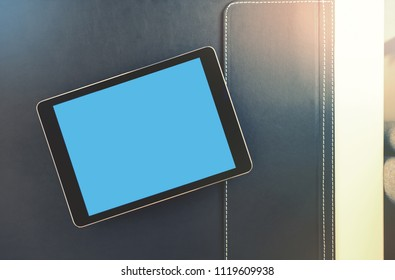 Mock up of black tablet computer on a desktop.  Clipping path included.