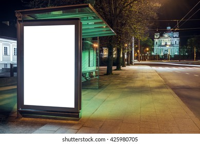 Mock up of blank bus stop vertical advertising light box at night