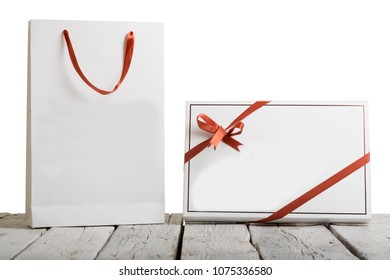 Mock up of blank craft white Paper Shopping Bag and Gift Box with red ribbon isolated on rustic wooden background. Copy space for text area.