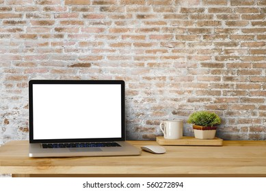 Mock up of blank laptop on the desk. Personal laptop computer on wood table over brick wall background.
