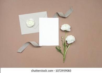 Mock up of blank paper card for wedding invitation or calligraphy with white flowers, ribbon and envelope on neutral beige background. Wedding templates flat lay, top view with copy space for text