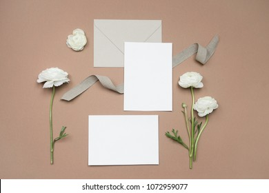 Mock up of blank paper cards for wedding invitation or calligraphy with white flowers, ribbon and envelope on neutral beige background. Wedding templates flat lay, top view with copy space for text
