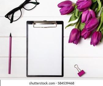 Mock up with blank paper, tulips and pink accessories. Workplace top view.