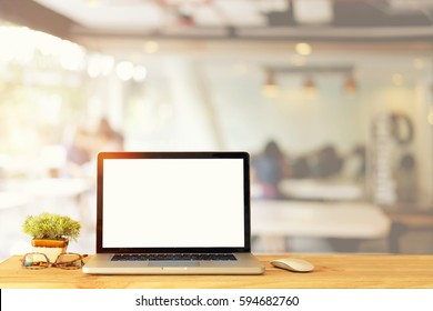Mock up Blank screen of Laptop on wood table in Co-working or cafe.