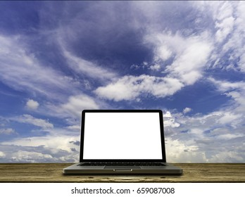 Mock up Blank screen of Laptop on old wooden desk with white cloud and blue sky background with clipping path
