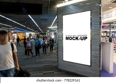 Mock up the blank signboard for advertising or information placed in front of the duty free shop in the airport terminal, has many passengers walks around, with clipping path