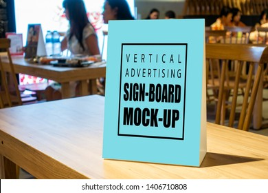 Mock up blank vertical advertising signboard in acrylic frame with clipping path on table in restaurant ,empty space for insert menu list or promotion