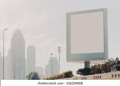 Mock up of blank vertical white advertising billboard in Dubai with residential and office modern contemporary skyscrapers and clean sky behind, plants and stone wall below