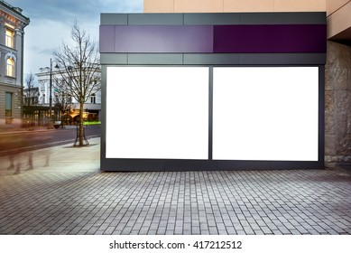 Mock up of blank white modern showcase in a city at night. Front view
