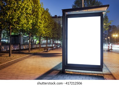 Mock up of blank white vertical light box on a bus stop in a city at night