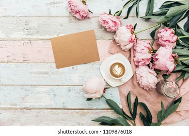 Mock up card. Flat lay cup of coffee and peonies on shabby chic background.