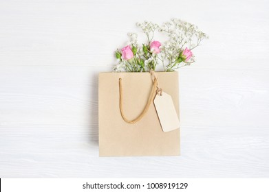Mock up Composition paper bag and tag of white flowers rustic style, for St. Valentine's Day with a place for your text. Flat lay, top view photo mock up