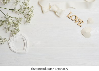 Mock up Composition of white flowers rustic style, hearts love and a gift for St. Valentine's Day with a place for your text. Flat lay, top view photo mock up.