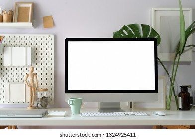 Mock up computer on loft workspace table showing blank white screen