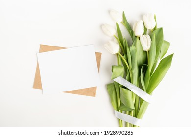 Mock up design. Fresh cut white tulip flowers and blank card with envelope top view on white background with copy space
