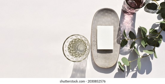 Mock up empty blank invitation card, ceramic plate cocktail glass and eucalyptus leaves on sunlit background. Summer mockup table setting  for wedding, business or menu. Long shadows
