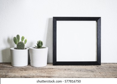 mock up frame with cactus pot on wooden floor