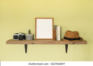 Mock up frame photo on wooden shelf. Lifestyle hipster decoration at home and travel concept