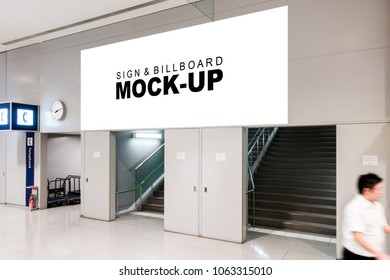 The mock up of horizontal blank billboard over on the entrance at  airport area, Empty space white screen for advertisement with clipping path, and blurred people walking
