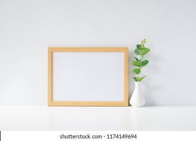 Mock up horizontal photo frame with green plant on table, home decoration.