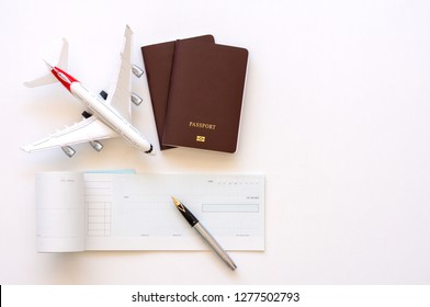 Mock up image of blank cheque book and two passports with airplane model on white background. Business trip and travel concept.