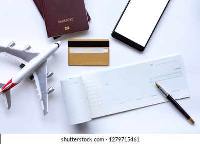 Mock up image of cheque book, mobile smart phone with empty blank screen, credit card, passport and airplane model on white background. Business trip and travel and paycheck concept.
