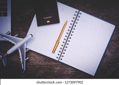 Mock up image of empty opened notebook, pen, passport, laptop computer and airplane model isolated on wooden background. Business trip and travel concept.