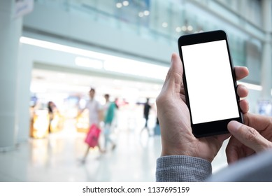 Mock up image, man hand holding blank screen mobile smartphone with abstract blurred background of people shopping interior department store, internet payment, online shopping concept