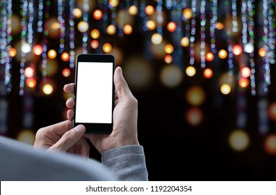 Mock up image of man hand holding blank screen mobile smart phone with colorful festive light bokeh of Christmas night party background