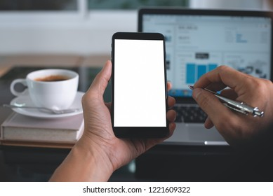 Mock up image of man hand holding blank screen mobile smart phone with laptop computer and cup of coffee on desk at office, over shoulder view