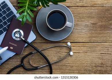 Mock up image of medical stethoscope,passport, laptop computer,air plane and cup of coffee isolated on old wooden background.Trip,travel and insurance concept.