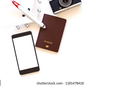 Mock up image of mobile smart phone with blank white screen, passport, camera and airplane model mock up isolated on white background. Technology and Travel concept.  Clipping path.