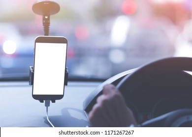 Mock up image of an unidentified man is driving taxi with smart phone blank screen. Image taken from back seat.