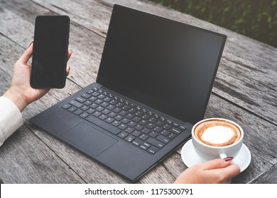 Mock up image of  woman hold smart phone and laptop on wood table, and one hand hold coffee cup.