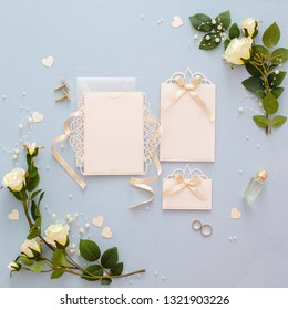 Mock up of invitation to wedding. Handmade greeting card. Frame from gentle white roses flowers on blue fabric background. Decorated background with artificial roses, beads and ribbons and card on it