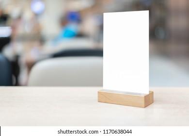 Mock up Label der leere Menürahmen in Bar Restaurant , Stand für Bücher mit weißen Blätter Papier Plexiglas Zelt Karte auf Holz Tisch Cafeteria unscharfen Hintergrund kann den Text des Kunden einfügen.