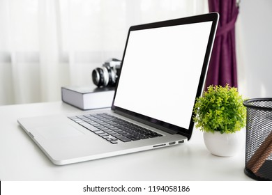 Mock up laptop with blank screen on table and note book, vintage camera