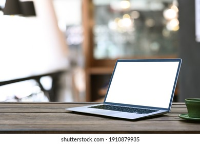Mock up laptop with blank screen on wooden table in coffee shop.