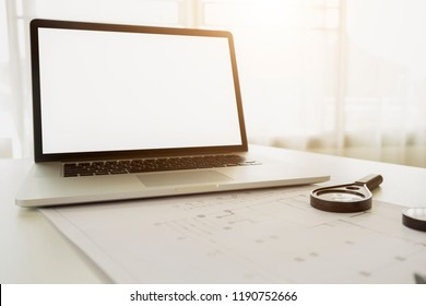 Mock up laptop with Engineer working on blueprint,Construction concept. Engineering tools.