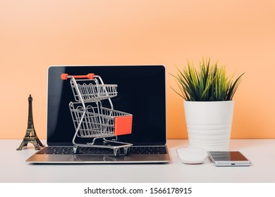 Mock up laptop notebook computer and shoppong online cart on desk table office soft yellow wall