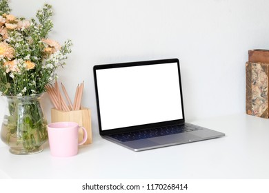 Mock up laptop and table of creative desktop of female designer with nobody. Beautiful flower bouquet and coffee mug with pencil.