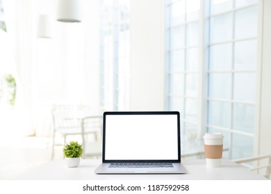 Mock up laptop. Workspace and coffee shop blur background.