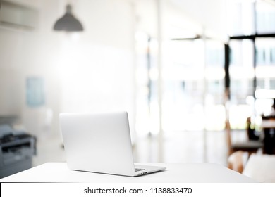 Mock up laptop. Workspace and office blur background.